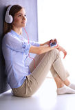 Smiling girl with headphones sitting on the floor Royalty Free Stock Images