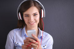Smiling girl with headphones sitting on the floor Royalty Free Stock Photo