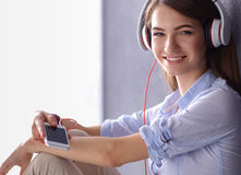Smiling girl with headphones sitting on the floor near wall Stock Image