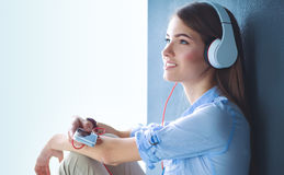 Smiling girl with headphones sitting on the floor near wall Royalty Free Stock Photography