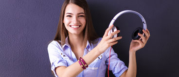 Smiling girl with headphones sitting on the floor near wall Stock Photo