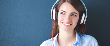 Smiling girl with headphones sitting on the floor near wall Stock Images