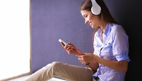 Smiling girl with headphones sitting on the floor near wall. Smiling girl with headphones sitting on the floor Royalty Free Stock Photos