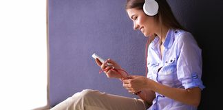 Smiling girl with headphones sitting on the floor near wall. Smiling girl with headphones sitting on the floor Stock Image