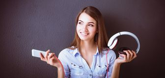 Smiling girl with headphones sitting on the floor near wall. Smiling girl with headphones sitting on the floor Stock Images