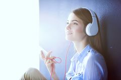 Smiling girl with headphones sitting on the floor near wall. Smiling girl with headphones sitting on the floor Stock Photography