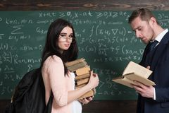 Smiling girl with heap of books standing in front of her stylish young professor concentrated on reading.  royalty free stock photo
