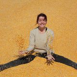 Smiling girl at heap of corn after harvest stock photo