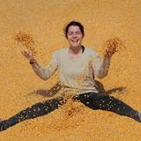Smiling girl at heap of corn after harvest stock photography