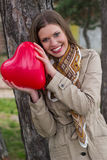 Smiling girl with heart in hands Stock Images