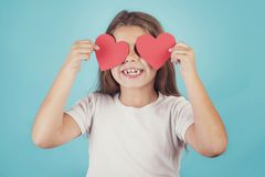 Smiling girl with hearts in her eyes. On blue background Stock Photos