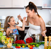 Smiling girl helping mother to cook. Happy smiling girl helping mother to cook at the kitchen Stock Image