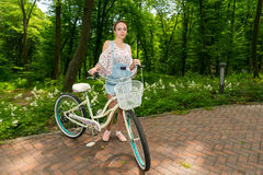 Smiling girl with her bicycle standing on bricks in a park Stock Photo