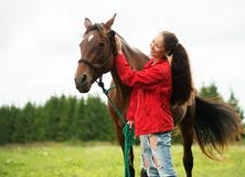Smiling girl with her brown horse Royalty Free Stock Images