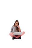 Smiling girl with her hand near face sitting on the floor with c Stock Image