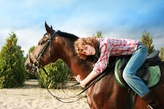 Smiling girl on her horse. And blue sky Stock Image