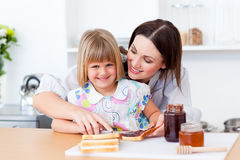 Smiling girl and her mother preparing toasts Royalty Free Stock Image