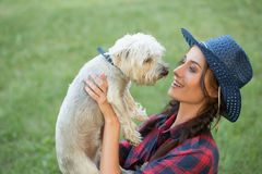 Smiling girl with her small dog. cowboy hat and. Plaid shirt. Outdoodrs Stock Images