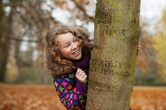 Smiling girl hiding behind a tree. Happily smiling teenager girl in colorful jacket hiding behind a tree in an autumn park Royalty Free Stock Images