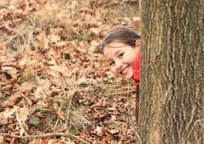 Smiling girl hiding behind tree Stock Photography