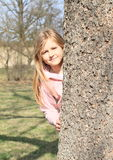 Smiling girl hiding behind tree Stock Images