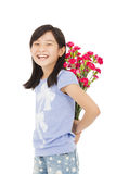 Smiling girl hiding a bouquet of carnations. In studio Stock Photography
