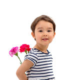 Smiling girl hiding a bouquet of red carnations isolated Stock Image