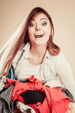 Smiling girl hold pile of clothes. Royalty Free Stock Photography