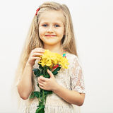 Smiling Girl hold yellow flowers. Royalty Free Stock Images