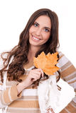 Smiling girl holding an autumn leaf royalty free stock images