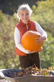 Smiling girl holding autumn pumpkin Stock Images