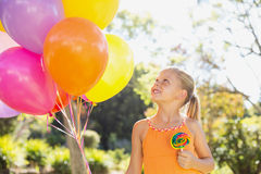 Smiling girl holding balloons and lollypop in the park Stock Images