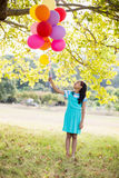 Smiling girl holding balloons in the park Stock Photo