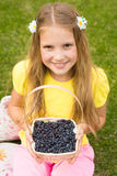 Smiling girl holding basket with berry Stock Images