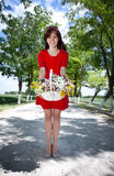 Smiling girl holding basket with flowers Royalty Free Stock Photo
