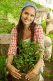 Smiling girl holding a basket with seedlings stock photo
