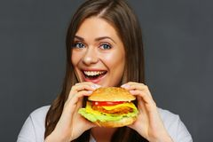 Smiling girl holding big burger. Isolated studio portrait Royalty Free Stock Photography