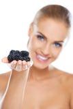 Smiling girl holding blackberries on hand Royalty Free Stock Images