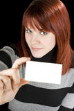 Smiling girl holding a blank card. Smiling redhead girl holding a blank business or greeting card. Studio shot stock images