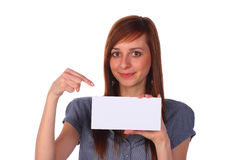 Smiling girl holding a blank note-card, isolated. Pretty smiling girl holding a blank note-card and pointing on it, isolated on white Royalty Free Stock Image