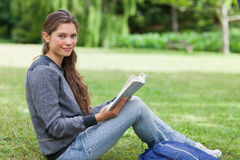 Smiling girl holding a book on her knees Royalty Free Stock Images