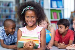 Smiling girl holding books against classmates Royalty Free Stock Photography