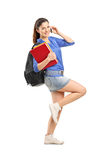 Smiling girl holding books and talking on a phone Stock Image