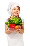 Smiling girl holding bowl full of fresh vegetables Stock Photo