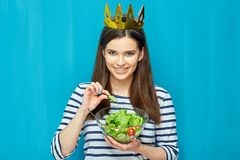 Smiling girl holding bowl with green salad. Blue wall background Stock Photography