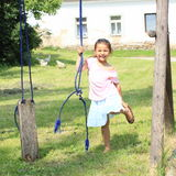Smiling girl holding a broken swing Royalty Free Stock Photography