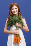Smiling girl holding bunch of carrot Stock Photo
