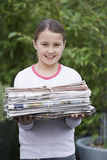 Smiling Girl Holding Bundle Of Waste Paper Royalty Free Stock Photography