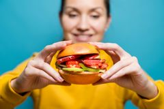 Smiling girl holding a burger of berries and fruits