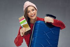 Smiling girl holding case and credit card, passport, ticket. Young woman ready for winter vacation travel Royalty Free Stock Photos